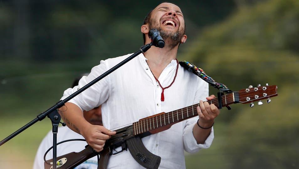 """El músico colombiano Cesar López toca su guitarra, que fusionó con una arma real, y llama """"Escopetarra"""". Foto: AP / Fernando Vergara"""