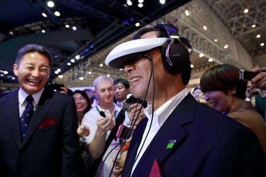 El presidente de Panasonic, Kazuhiro Tsuga, prueba los anteojos de video 3D de Sony; detrás ríe Kazuo Hirai, presidente de Sony. Foto: Reuters