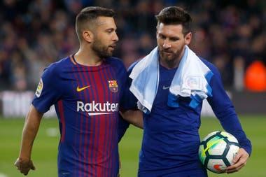 Lionel Messi se lleva la pelota tras un nuevo hat-trick. Lo saluda Jordi Alba