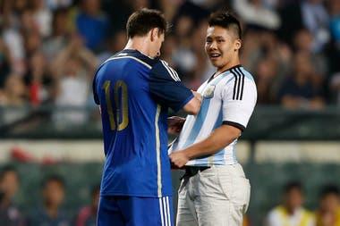 Messi firma un autógrafo para un fanático que invadió el campo durante un amistoso contra Hong Kong el 14 de octubre de 2014. Argentina ganó 7-0