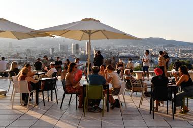 La gente se sienta en un bar cerca del Museo Nacional de Arte de Barcelona