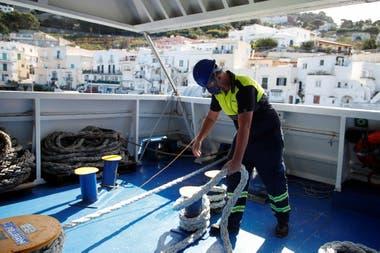 Un empleado del ferry de Capri, realiza maniobras para la partida de la embarcación