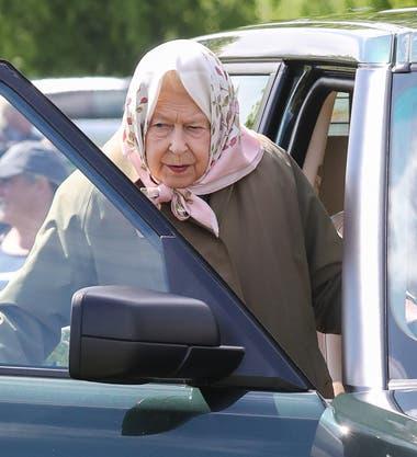 Preparada para la lluvia. Isabel II llevó un impermeable de gabardina y uno de sus coloridos pañuelos de seda cubriendo su cabeza.