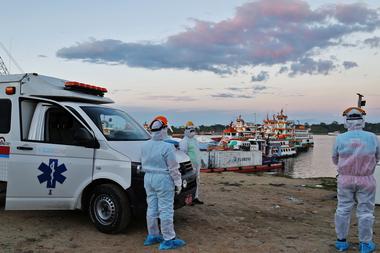 El personal médico espera a los pacientes con coronavirus traídos de las comunidades cercanas, en un puerto en el río Amazonas, en Iquitos, Perú, el 18 de junio de 2020