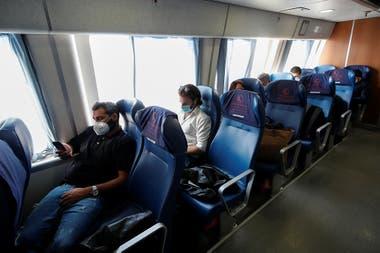 Pasajeros de un ferry utilizan barbijos y mantienen distancia social al viajar con el asiento del pasillo vacío, en Capri, Italia