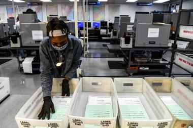 Se ve a un trabajador electoral durante el proceso de escaneo de boletas de votación por correo en el Departamento de Elecciones del Condado de Miami-Dade en Miami, Florida, el 21 de octubre de 2020