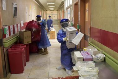 Los trabajadores médicos organizan los desechos y suministros a la entrada de la unidad de cuidados intensivos del hospital IESS Carlos Andrade Marín en Quito, el 17 de junio de 2020