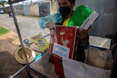 De pie, detrás de la ventana del protector de plástico de su aula móvil, Gerardo Ixcoy sostiene una caja de pizza como parte de una lección sobre fracciones