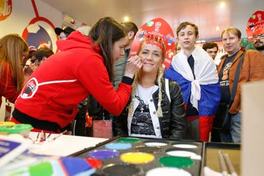 Una maquilladora pinta la bandera rusa en la cara de una visitante en la tienda oficial del FIFA Fan Fest en Moscú