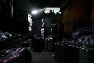 Una vendedora en el mercado nocturno Pegatron en Shangai. La demanda más baja de bienes de consumo ha provocado que se pierdan empleos y que los sueldos sean más bajos y agudiza la desaceleración económica de China