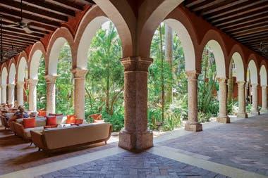 Arcos de medio punto sobre columnas de piedra coralina rodean el jardín frondoso. Corredores de sombra donde sentarse a contemplar fijamente ese centro verde, porque el mundo exterior parece haber dejado de existir.