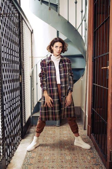 Tapado de lana en cuadrillé (Vitamina), polera y pantalón de cuero con frunce en la cintura y en los puños (Giesso), zapatillas bota de cuero blanca (Prüne)