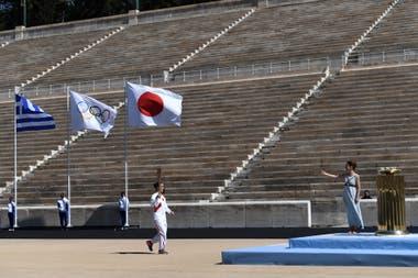 Las banderas de Grecia, de Japón y la olímpica flamean durante la ceremonia de entrega de la llama olímpica