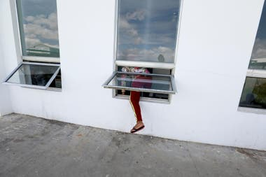 Una trabajadora entra por la ventana para volver al trabajo después de una hora de almuerzo