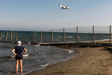 Un bañista se para en la orilla del mar mientras un jet hace su descenso hacia el Aeropuerto Internacional de Larnaca de Chipre el 1 de agosto de 2020