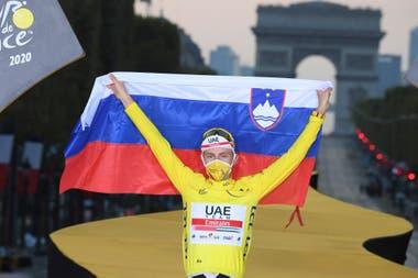 Con la bandera de su país, el esloveno Tadej Pogacar festeja su mayor triunfo