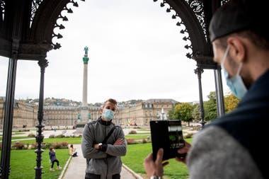 Dos turistas usan máscaras faciales en el Pabellón de Música de la Schlossplatz y se toman fotografías con el Palacio Nuevo y la Columna del Jubileo, en Stuttgart, Alemania