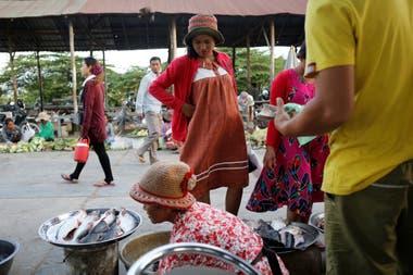 Khen Srey Touch, de 27 años, embarazada de nueve meses, compra comida en un mercado afuera de Complete Honor Footwear Industrial