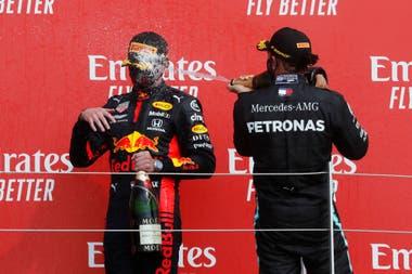 Max Verstappen recibe el baño de champagne de Lewis Hamilton en el podio de Silverstone; el neerlandés saltó al segundo puesto del Campeonato de Pilotos que lidera el séxtuple campeón británico