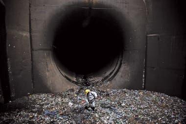 Un operario retira basura del canal aliviador del arroyo Maldonado, donde cada día sacan decenas de toneladas de residuos. Foto:Santiago Filipuzzi