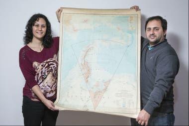 Silvina y Rubén sostienen un mapa de la Antártida Argentina