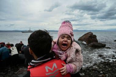 Una niña llora al llegar en bote con otros 54 refugiados afganos a la isla griega de Lesbos el 28 de febrero de 2020