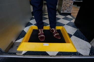 Para aumentar la prevención del contagio se podría aplicar una alfombrilla con líquido desinfectante para limpiar la suela del calzado antes de ingresar al local