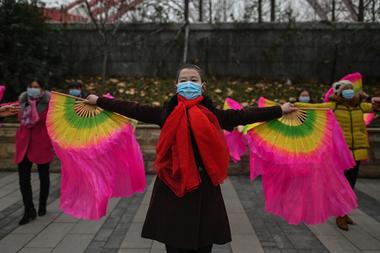 Mujeres con mascarillas como medida preventiva contra el coronavirus bailan en una calle en Wuhan, en la provincia central de Hubei, China el 23 de enero de 2021, un año después de que la ciudad entrara en bloqueo para frenar la propagación del coronavirus