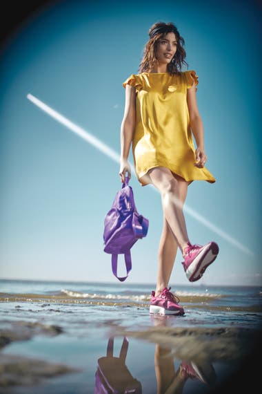 Vestido de seda brillosa (Las Pepas), zapatillas fucsias (Nike), mochila satinada violeta y turbante de raso (Las Pepas)