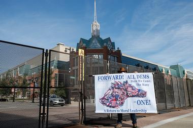 El manifestante Stephen Parlato sostiene un cartel fuera del Centro de Wisconsin antes de la Convención Nacional Demócrata en Milwaukee, el 17 de agosto de 2020