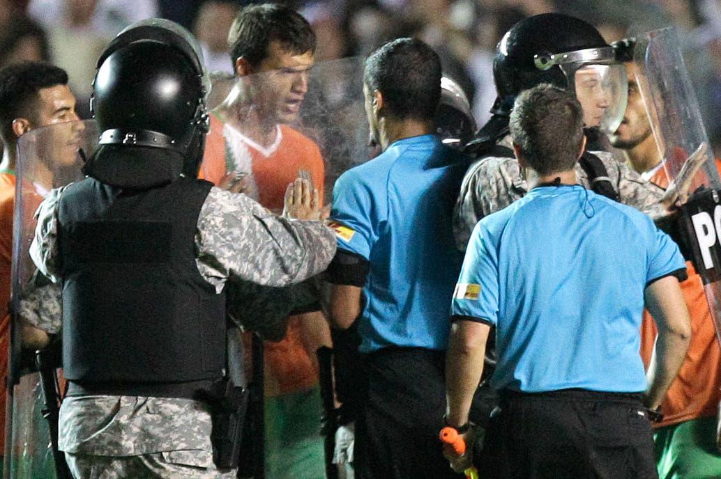 Civelli encabeza las quejas de los jugadores de Banfield con el árbitro Ricci, tras el partido; la policía intervino y golpearon a algunos futbolistas