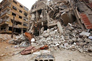 Un soldado de las fuerzas gubernamentales sirias camina entre los escombros en Zamalka, al este de Ghouta, el 11 de abril