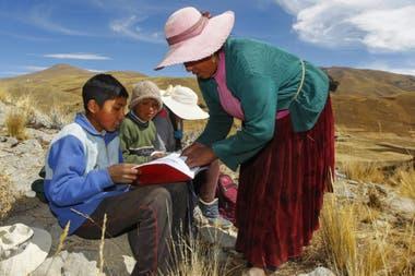 Raymunda Charca ayuda a sus hijos Juan Carlos, de 13 años, Álvaro, de 10, y Roxana Cabrera, de 16, en la cima de una colina donde pueden recoger la señal en sus celulares para recibir clases virtuales cerca de su casa en la remota comunidad de Conaviri, distrito de Manazo, en los Andes peruanos, cer