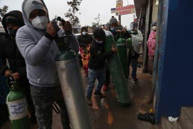 Un grupo de personas espera frente a un depósito para recargar sus tubos de oxígeno, en el barrio San Juan, en Lima