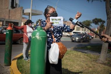 En Gallo, Perú, Lydia Ruiz habla con un periodista cerca de un tanque de oxígeno recién llenado para su hermana, que sufre de COVID-19.
