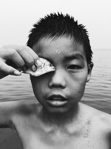 """""""Conocí a este chico mientras caminaba por la orilla del mar en YanTai Shandong, China. Cuando estaba tratando de sacarle una foto, él pone el pescado que atrapó delante de su ojo"""""""