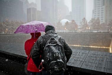 Bajo una intensa nevada dos personas visitan el Memorial 9/11 en Nueva York