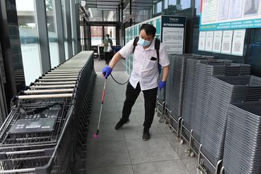 Un trabajador desinfecta canastas de compras y carritos en la entrada de un supermercado en Pekín el 17 de junio de 2020