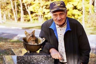 Bill Wynne junto a un monumento en homenaje a su perra Smoky, que fue levantado en un parque de Cleveland en el año 2005 por veteranos de guerra