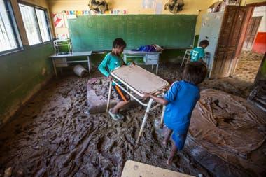 Dos chicos mueven un pupitre en su escuela llena de lodo
