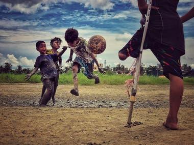 Un niño que perdió una pierna mira a sus amigos jugar al fútbol en Yangon, Myanmar