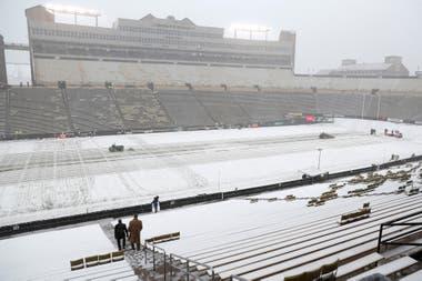 Un par de fanáticos se dirigen a sus asientos en Folsom Field mientras personal del estadio limpia la nieve del campo antes de la primera mitad de un partido de fútbol americano universitario de la NCAA el sábado en Boulder, Colorado