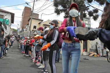 Las personas se pasan ladrillos que quedaron tirados en las calles luego de las protestas.