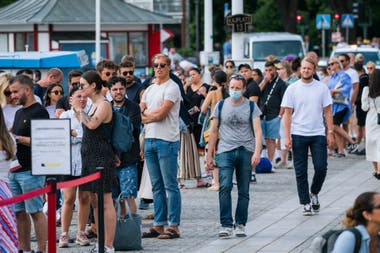 Un hombre con tapabocas camina junto a los viajeros mientras hacen cola para abordar un barco en Stranvagen, en Estocolmo, el 27 de julio pasado