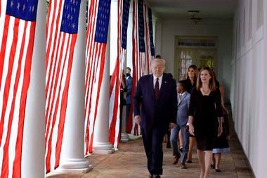 En esta foto de archivo tomada el 26 de septiembre de 2020, Donald Trump (izquierda) y la jueza Amy Coney Barrett (derecha), con la primera dama de Estados Unidos, Melania Trump, llegan al jardín de rosas de la Casa Blanca en WashingtoN