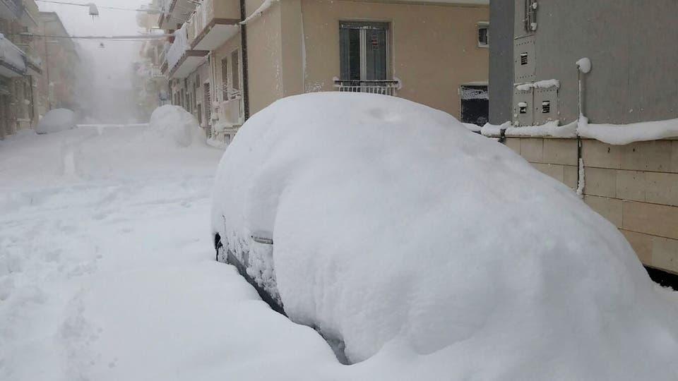 Las calle y los autos totalmente cubiertos de nieve en un pueblo de Italia. Foto: AFP