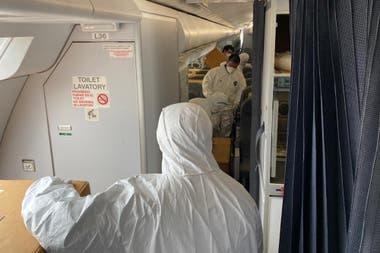 Operarios del aeropuerto de China, distribuyen la carga en la cabina