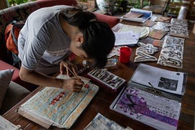 En esta foto tomada el 7 de agosto de 2020, la activista climática Howey Ou, de 17 años, pinta algunos letreros y carteles en su hotel en Guilin