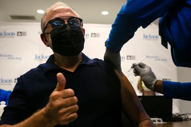 Emilio Estefan, 67, productor musical internacional, levanta el pulgar mientras recibe su primera dosis de la vacuna Pfizer-BioNtech contra la Covid-19 en el Centro de Rehabilitación Christine E. Lynn, en Miami, Florida, el 30 de diciembre de 2020