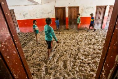 Los chicos chapotean en el barro que cubre el suelo de la escuela